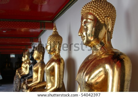 The row of golden statues of Buddha in thai temple