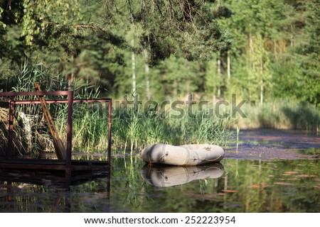 the rubber boat anchored on the water - stock photo