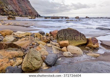 The rugged coastline on Northern Yorkshire with the wonderful rockpools and and varied rockfalls from the nearby cliffs. - stock photo
