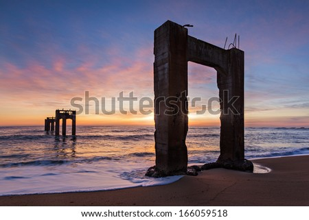 The ruins of an old concrete pier near Davenport, California on reaching out into the Pacific Ocean during Sunset.  - stock photo