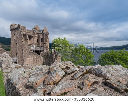 The ruins of Urquhart Castle sit at Loch Ness. This royal castle played an important role in the Scottish wars for independence and thousands of people visit it each year - stock photo