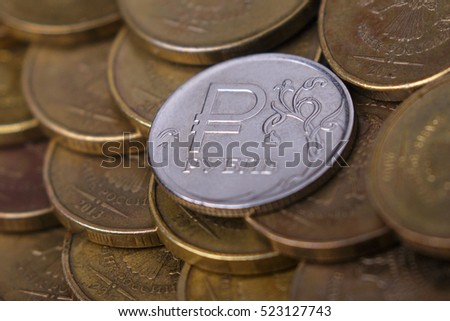 The Russian rouble coin with rouble sign and gold money on the desk.