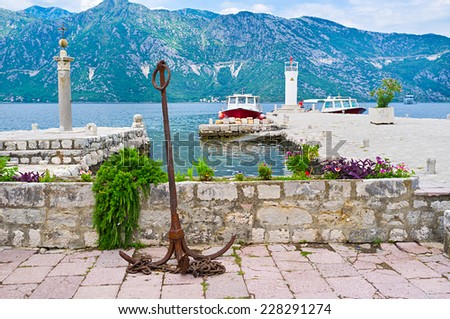The rusty anchor set as the decoration on Our Lady of the Rocks islet next to the tiny harbor for tourist boats, Perast, Montenegro. - stock photo