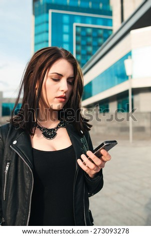 The sad confused woman speaks by phone on the street - stock photo