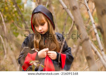 The sad girl in a red and black cloak in the forest - stock photo