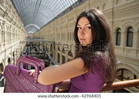 The sad girl stand against the big glass roof in shop - stock photo