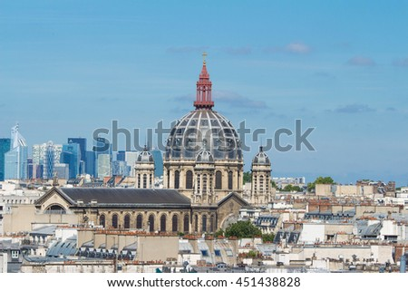 The Saint Augustin church and parisian houses with modern skyscrapers of business La Defense district in the background , France.