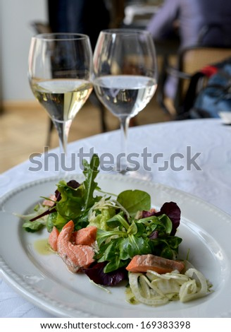 The salad with salmon is situated on the white plate. The salad contains: salmon, rocket (arugula), leaf lettuce, basil (or sweet basil)... and plant oil.