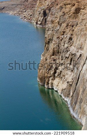 The salty shore of the Dead Sea on the Jordan side, with slat formations. The markings on the rock face indicate that the waters are receding. - stock photo