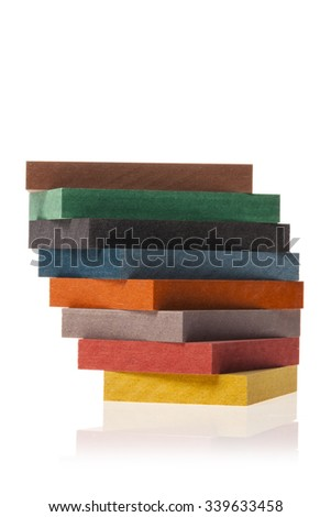 The sample of the colorful valchromat(eco-wood board) stacked up, brown, green, black, blue, orange, grey, red, yellow for ecological interior, nature isolated white. - stock photo