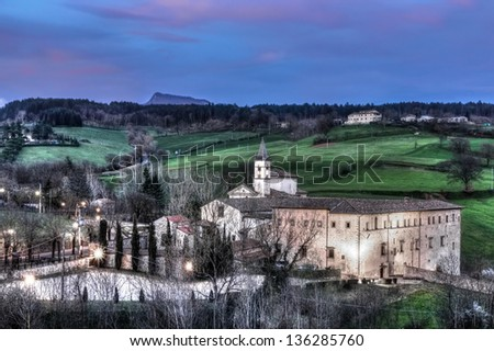 The sanctuary of Santa Maria del Sasso near the small town of Bibbiena (Tuscany - Italy) in a picturesque view of the sunset. In the background is the mountain of La Verna. - stock photo