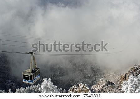 The Sandia Mountain tram rises out of the clouds of an early winter storm - horizontal - stock photo