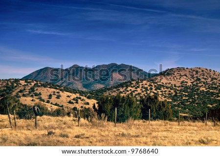 The Sandia Mountains captured in the desert of New Mexico just east of the city of Santa Fe in a rural and country setting - stock photo