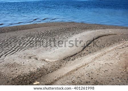 the sandy beach at a blue lagoon - stock photo