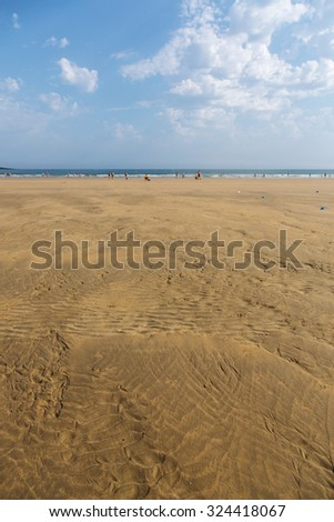 The sandy beach of the Atlantic Ocean. South of France. Basque Country. Hendaye. Blue sky with high clouds and yellow sand. horizon line in the middle. space for inscriptions.