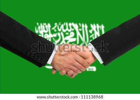 The Saudi Arabia flag and business handshake - stock photo