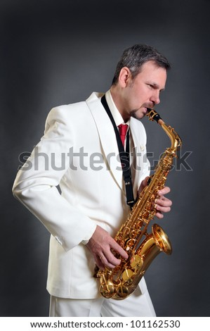 The saxophonist in a white  jacket - stock photo