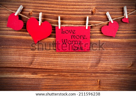 The Saying Love More Worry Less on a Red Label with Hearts Hanging on a Line on a Wooden Background - stock photo
