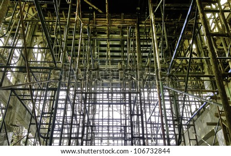 The scafffolders and bared concrete during the renovation at the construction site. - stock photo
