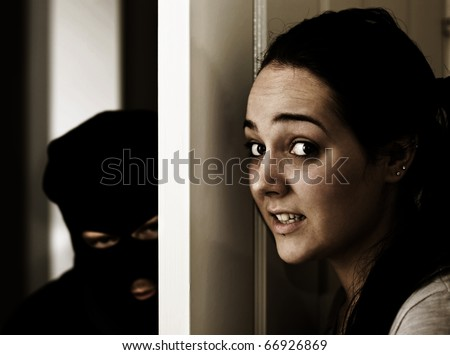 The Scene Of A Home Invasion Where A Masked Man Creeps In The Front Doorway - stock photo
