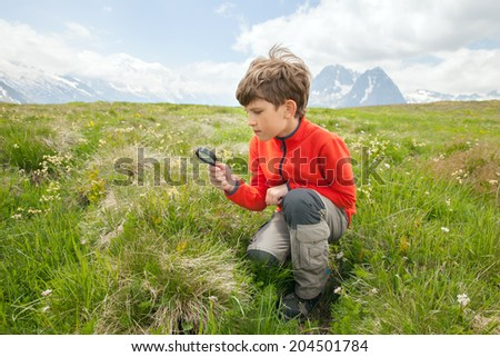 The schoolboy with magnifier glass on Alpine meadow