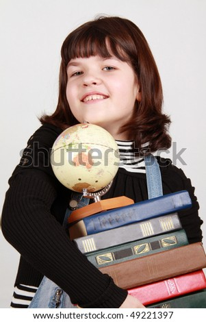The schoolgirl holds a pile of books and the globe - stock photo