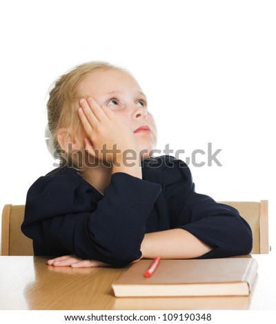 The schoolgirl is sitting at his desk and dreams on a white background.