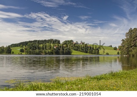 The Schwalten pond in allgaeu is an idyllic lake which is used today as a bathing lake and fish farming - stock photo