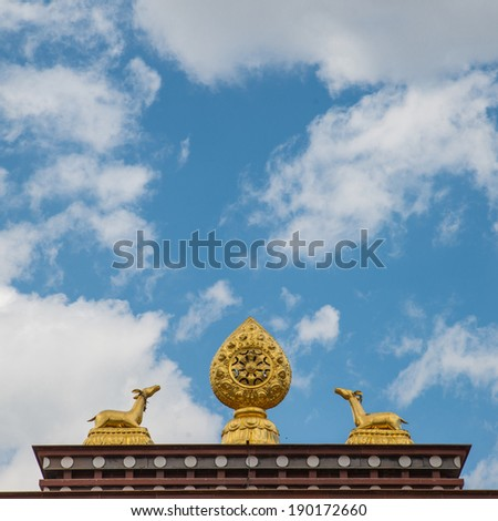 The sculpture of the wheel of Dharma and two deer on the roof - stock photo