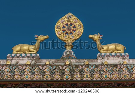 The sculpture of the wheel of Dharma and two deer on the roof of the gate of the monastery Tengboche - Nepal - stock photo