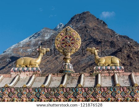 The sculpture of the wheel of Dharma and two deer on the roof of the gate of the monastery Tengboche with mountains on background - Nepal - stock photo