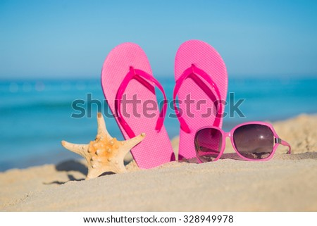 The sea, beach, sand and women's accessories: pink flip-flops, sunglasses and starfish - stock photo