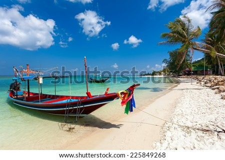 The sea coast with turquoise water, wooden boats and palm trees ashore. - stock photo