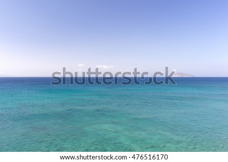 The sea of different colors of blue and a small mountain