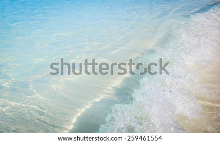 The sea water wave hit the sandy beach on uninhabited island Half Moon Cay (The Bahamas). - stock photo