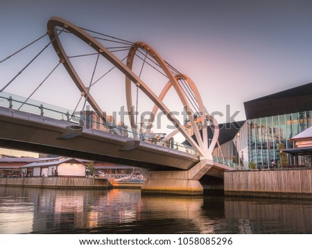 The Seafarers Bridge, a footbridge over the Yarra River between Docklands and South Wharf in Melbourne, Victoria, Australia at dusk as the sun is setting.
