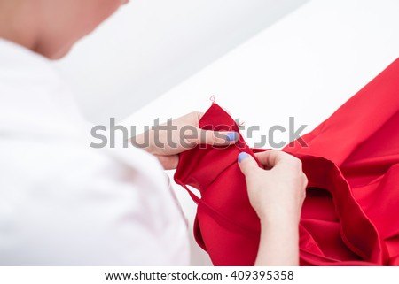 the seamstress is making the pattern in a sewing workshop. a tailor sews red dress - stock photo