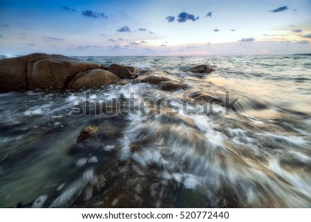 The seascape of waves and rocks in Thailand with movement of shutter speed blur at the dawn time