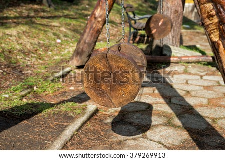 The seat of a swing made of tree trunks hung on chains