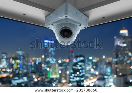 The security cameras on a balcony high building. City view at night with blurred light - stock photo