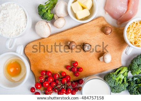 The selection of ingredients for the preparation of traditional French dishes quiche lorraine, on white wooden table with wooden cutting board, top view