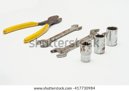 the selective focus of rusted tools over white background.  - stock photo