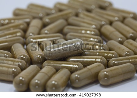 The selective focus of the pill capsule heap onto the white background - stock photo