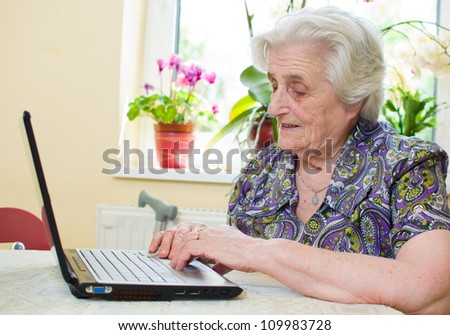 The senior hand presses the laptop keyboard button - stock photo