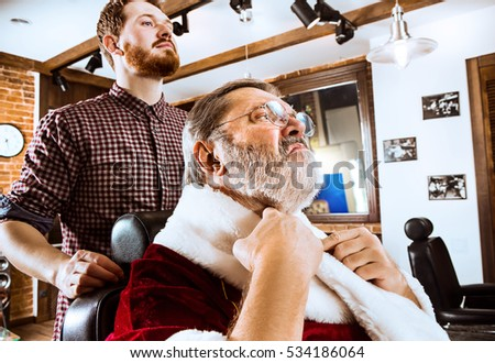 The senior man in Santa claus costume shaving his personal master at barber shop before Christmas