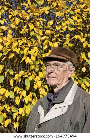 The senior man portrait in autumn sunny day. - stock photo
