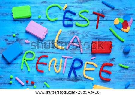 the sentence cest la rentree, back to school in french, written with modelling clay of different colors on a blue rustic wooden background - stock photo