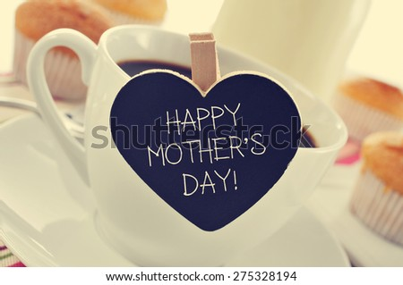the sentence happy mothers day written in a heart-shaped blackboard placed in a cup of coffee, with some muffins in the background in a set table for breakfast - stock photo