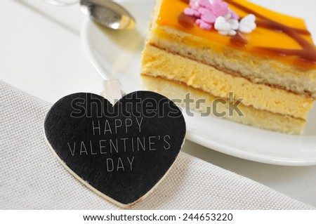 the sentence happy valentines day written in a heart-shaped chalkboard, and a piece of cake on a set table - stock photo