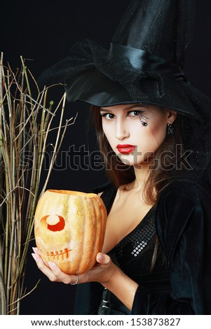 The serious brunette witch with a broom and pumpkin over black background in studio